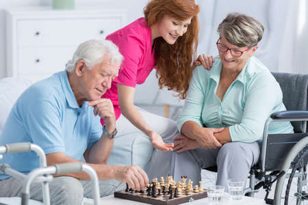 Senior patients with walking problems playing chess with carer