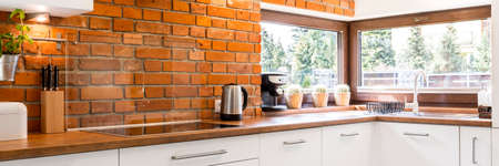 cocinas industriales: Modern kitchen corner with a stylish brick wall and a large horizontal window Foto de archivo