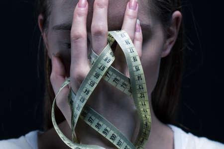 Anorexia meisje die haar gezicht met een centimeter Stockfoto