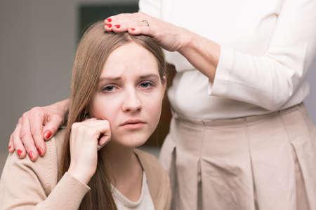 terapia psicologica: Retrato de una triste mano de niña y mujer adolescente sosteniendo en su brazo y la cabeza