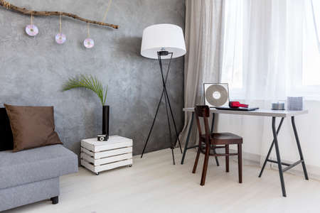 cement wall: Image of a grey living room with cement wall effect, sofa, floor lamp, desk and chair