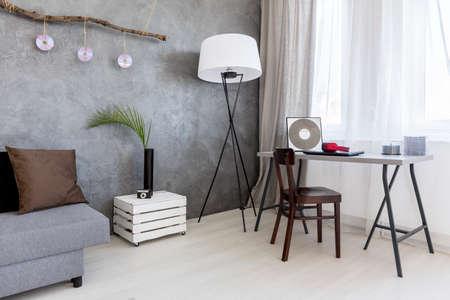 Imagen de una sala de estar gris con efecto de pared de cemento, sofá, lámpara de pie, escritorio y silla Foto de archivo