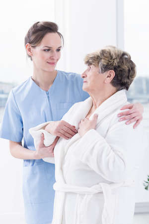 Senior woman in bathrobe looking at young nurse standing close to her