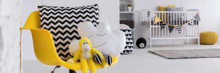 amarillo y negro: Primer plano de la silla amarilla en la habitación del bebé con la almohadilla nube de forma linda y mono de juguete. En el fondo de la cuna blanca