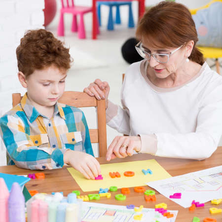 Teacher and boy learning alphabet with plastic letters