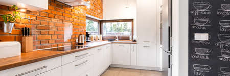 kitchen cabinets: Bright and clean modern minimalist kitchen with white cabinets, brick wall and glass splashback