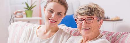 apoyo familiar: hija feliz y su madre senior sentados juntos en un sofá, panorama