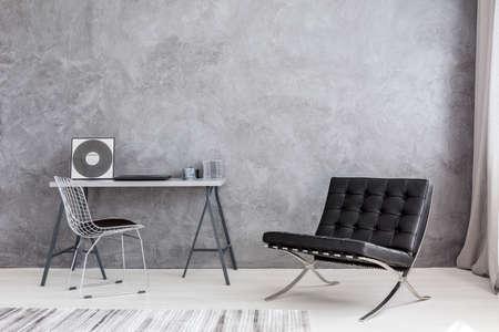 灰色の壁、モダンな椅子、ラウンジチェア、シンプルな机の上に横になっている cd の音楽コレクションと禁欲的なインテリア 写真素材