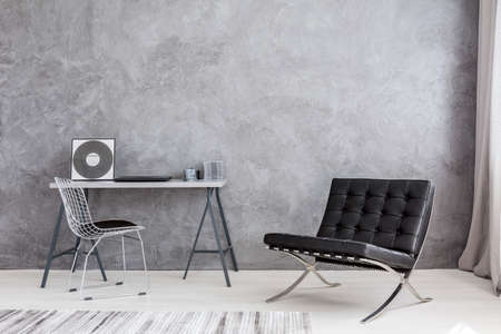 Ascetic home interior with grey wall, modern chair, lounge chair, cd music collection lying on a simple desk Foto de archivo