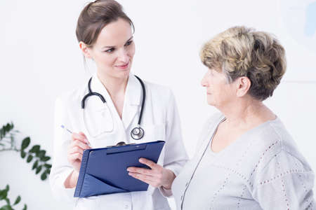彼女の前に立っている高齢者の女性で既往症女性医師