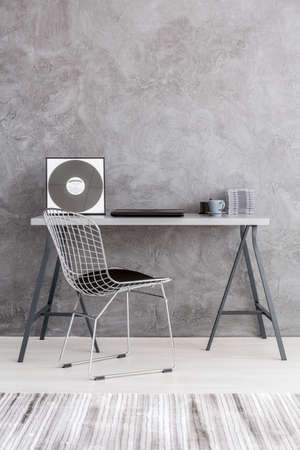 ascetic: Grey interior with a cement wall effect, modern chair, cd music collection lying on a simple desk Stock Photo