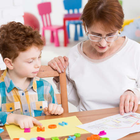 Boy and teacher setting words from colorful letters 版權商用圖片