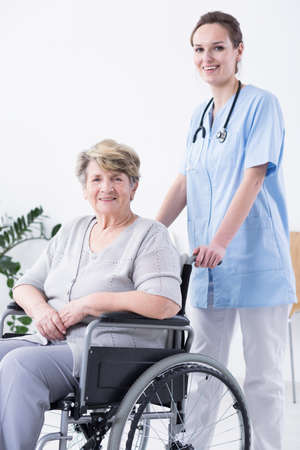 Young female nurse standing behind woman on a wheelchair Stock Photo