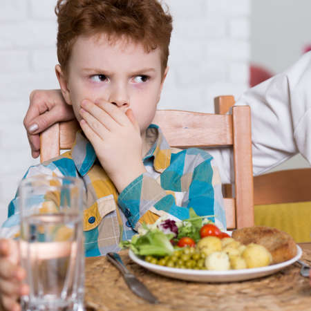 refusing: Young boy refusing to eat healthy dinner Stock Photo