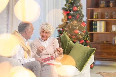 atmosfera: Mujer mayor feliz que sostiene el regalo de Navidad de su marido