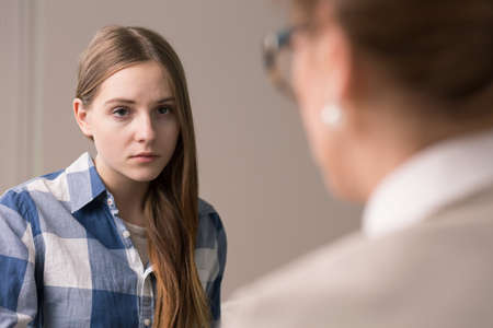Sad and depressed teenager talking with psychologist Stock Photo