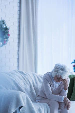 alone sad: Despair senior woman sitting alone on sofa during christmas