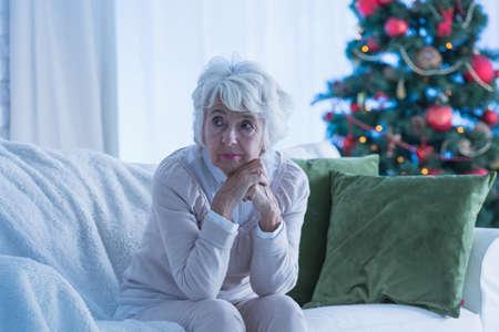 Senior vrouw zit alleen op de bank, kerstboom op de achtergrond Stockfoto
