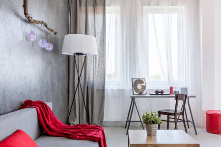 ascetic: New style ascetic home interior in grey with sofa, small table, desk, floor lamp and red details