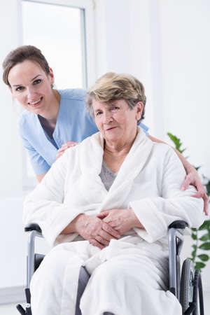 Elder woman sitting on a wheelchair in bathrobe with young nurse behind her