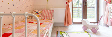 balcony window: Cosy little girls bedroom with close-up of a metal bed and a large balcony window overlooking the garden