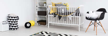 babys: Close-up of room corner with white babys cradle and shelf made of wooden boxes. Next to it black chair with pillows