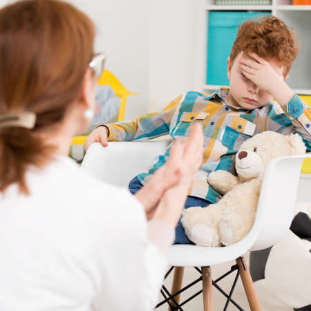 psychologists: Boy sitting at the chair in child psychologists office Stock Photo
