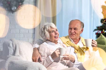 holiday spending: Senior husband and wife sitting on sofa, celebrating christmas evening