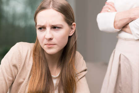 Sad teenage girl , in the background woman standing with her arms crossed