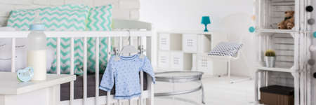 babys: Close-up of white cradle with pretty pillows in babys room. Next to it on night stand bottle with milk and teat Stock Photo