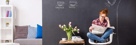 periodicos: niña inteligente de lectura de periódicos en una moderna cafetería. Al lado de su mesa con abucheos y café, en el fondo cómodo sofá y estante Foto de archivo