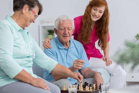 apoyo familiar: pareja de alto nivel y buen cuidador de ajedrez que juegan juntos Foto de archivo
