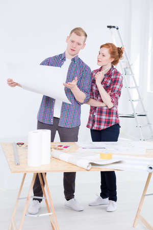 Man and the woman standing together close to the drafting board and consulting the project with the ladder behind