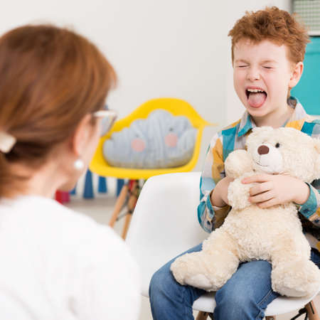 color therapist: Naughty child holding teddy bear at psychologists office