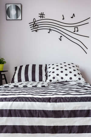 Shot of a black and white bedroom with a stave painted on a wall, decorated in a subtle way Imagens