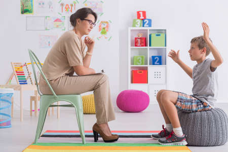 Angry young boy sitting on a pouf, talking with psychologist Stock Photo