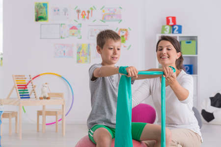 Physiotherapist and boy sitting on a gym ball exercising with a rubber tape