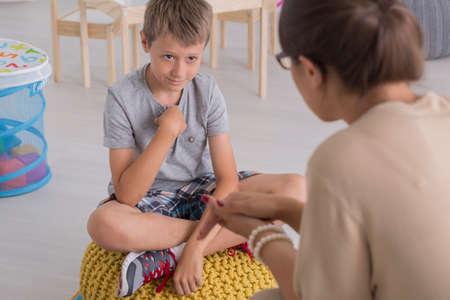 Droevige jonge jongen zittend op een poef, praten met een psycholoog