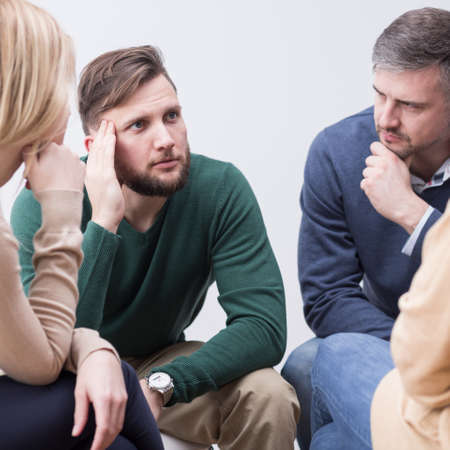 Verontruste jongeman die zijn ondersteunende psychotherapiegroep toevertrouwt