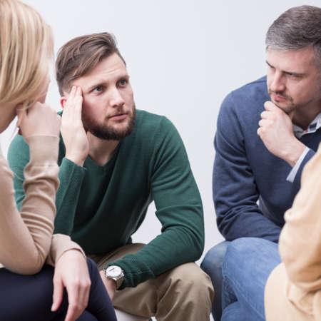 Zakłopotany młody mężczyzna zwierza się swojej wspierającej grupie psychoterapeutycznej