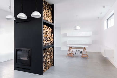 Spacious, minimalist, white home office and modern black fireplace with firewood