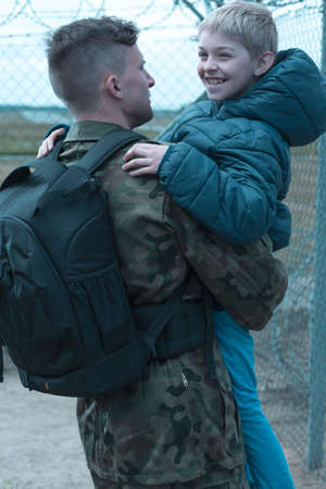 Soldier holding his happy son in his arms Stock Photo
