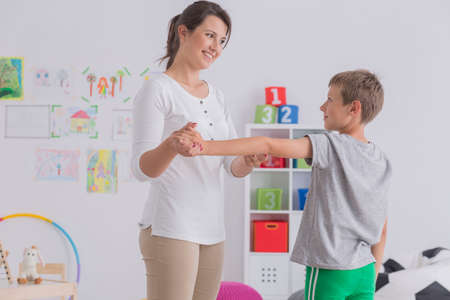 Small boy exercising with a professional physiotherapist
