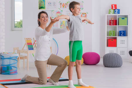 Young physiotherapist exercising with a happy school-boy