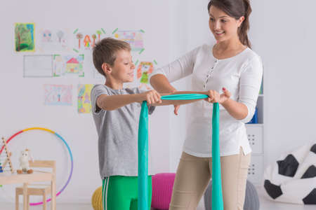 Physiotherapist and child exercising with a rubber tape