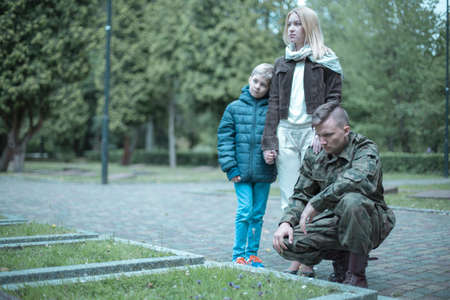Photo of a soldier and his family visiting grave Stok Fotoğraf