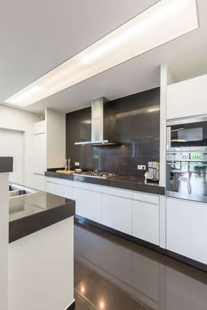 Modern and light kitchen with modern furniture and shining tiles