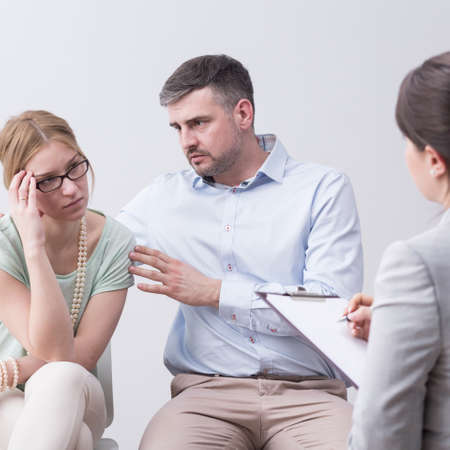 Caring man cheering up his worried wife on psychotherapy