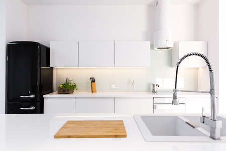 Cozy, white, lacquer kitchen in modern house with black retro fridge Standard-Bild - 122034826
