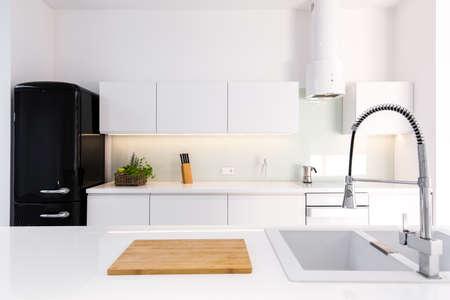 Przytulna, biała, lakierowana kuchnia w nowoczesnym domu z czarną lodówką retro